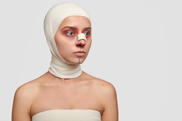 Colpo laterale di paziente premuroso con bendaggio medico sul naso, operato da estetista Foto Gratuite