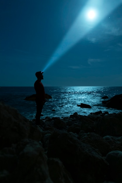 Sideways silhouette of a man looking at the sky Free Photo