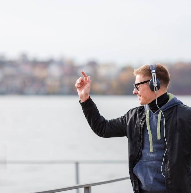 コピースペースで外で音楽を聞いて横スマイリー金髪男 無料写真
