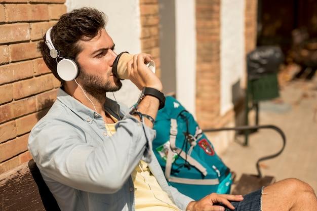 Sideways traveler drinking coffee Free Photo