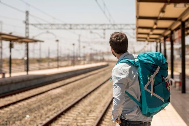 Sideways traveler looking for train Free Photo