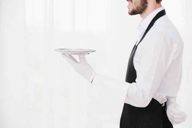 Sideways waiter holding metal plate Free Photo