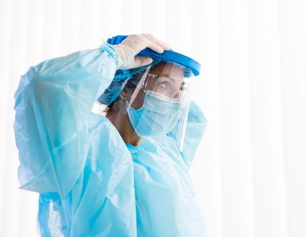 Боковой женщина-врач надевает защитную одежду Premium Фотографии
