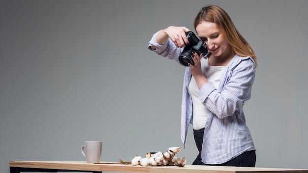 Боком женщина держит профессиональную камеру и фотографировать еду Бесплатные Фотографии