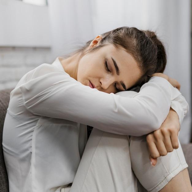 Donna di lato che sembra triste mentre lavora da casa Foto Gratuite