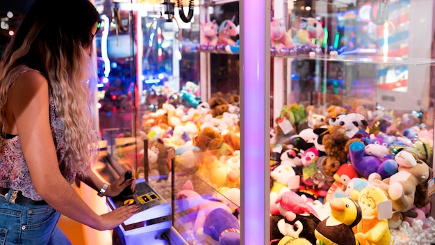 Sideways woman playing arcade machine Free Photo