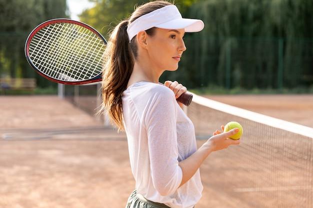 Sideways woman playing tennis Free Photo