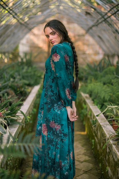 Sideways woman posing in a green house looking at camera Free Photo
