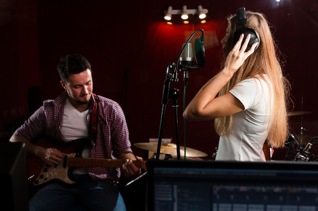 Sideways woman singing and guy sitting with a guitar Free Photo