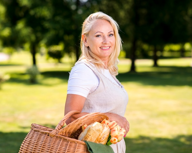 Sideways woman with a basket looking at the camera Free Photo