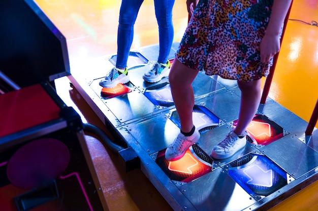 Sideways women playing dancing arcade Free Photo