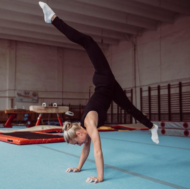 Боковой молодая блондинка тренируется для чемпионата по гимнастике Бесплатные Фотографии