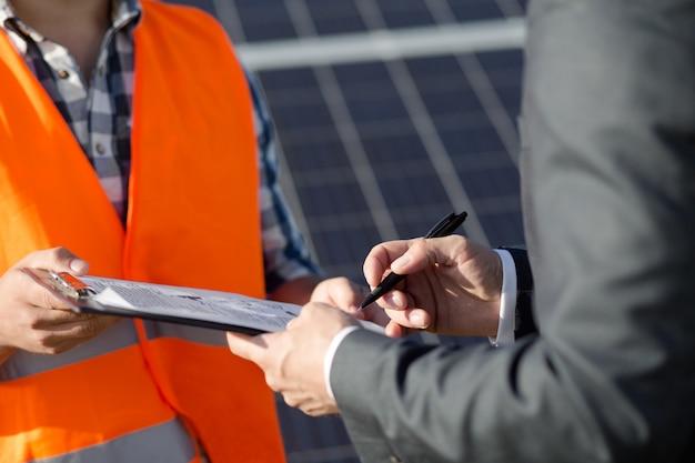 Закройте вверх по взгляду на контракте мастера и клиента sigining на солнечной электростанции. Premium Фотографии