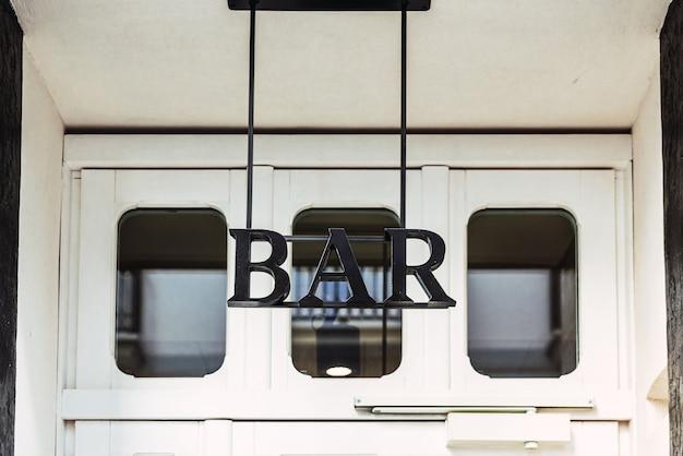Подпишите с надписью bar на двери паба, где можно купить напитки. Premium Фотографии