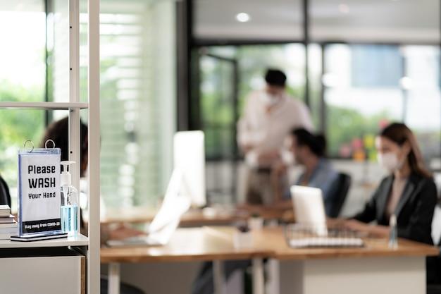 営業再開後の衛生練習用のオフィス周辺の手の消毒剤の看板。 covid-19ウイルスの拡散を防止するために働くビジネスマンが新しい通常のオフィスでフェイスマスクを着用 Premium写真