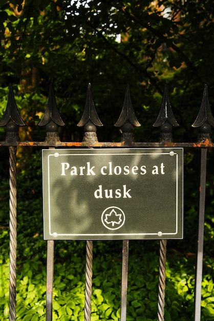 Signboard with text park closes at dusk Free Photo
