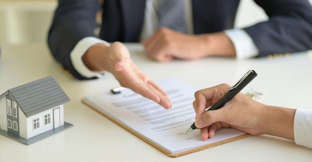 Подписание договора купли-продажи дома между брокером дома и клиентом. Premium Фотографии