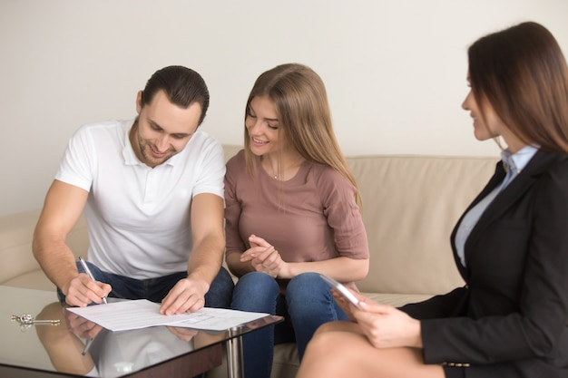 Signing agreement on meeting with realtor, couple buying renting apartment Free Photo