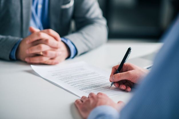 Signing contract on a meeting, close-up. Premium Photo