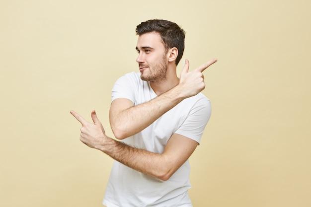 Знаки, жесты и язык тела. изолированный снимок красивого молодого небритого кавказского парня, указывающего указательными пальцами в противоположных направлениях, смущенный взгляд, не знающий верного пути, потерянный Бесплатные Фотографии