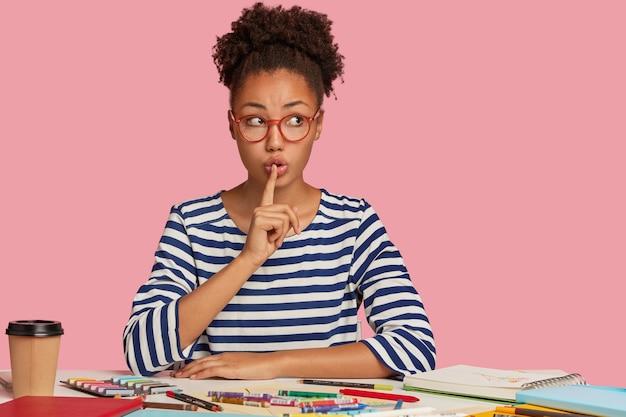 Silenziosa donna nera fa un gesto di silenzio, ha i capelli ricci pettinati in uno chignon, guarda segretamente da parte, indossa un maglione a righe, chiede di non fare rumore, ha l'ispirazione per disegnare, modelli sul muro rosa Foto Gratuite