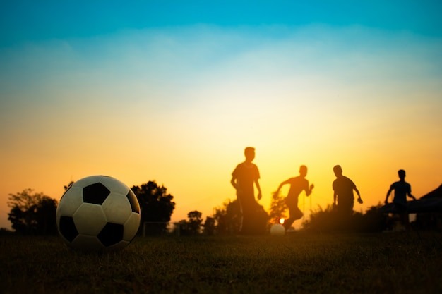 Silhouette action sport outdoors of a group of kids having fun playing soccer football Premium Photo