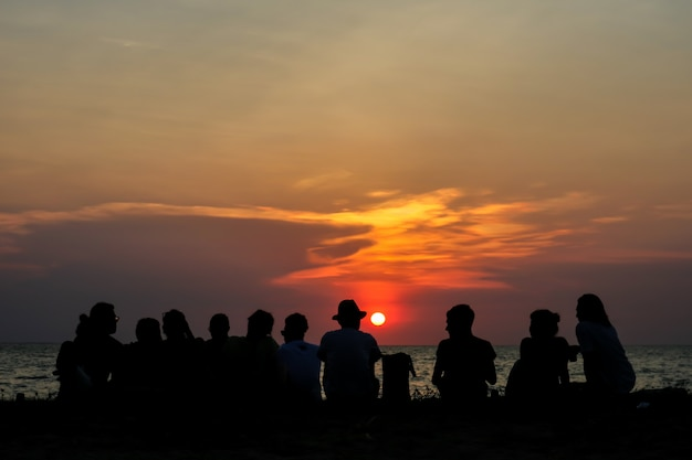 Silhouette all people in family meeting look sunset sky on beach Premium Photo