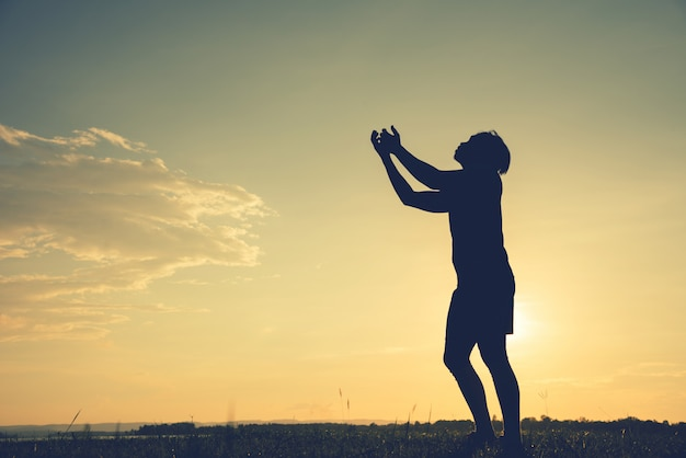 Silhouette of a asian man fists up at sunset background Premium Photo