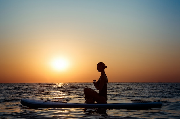 Silhouette of beautiful woman practicing yoga on surfboard at sunrise. Free Photo