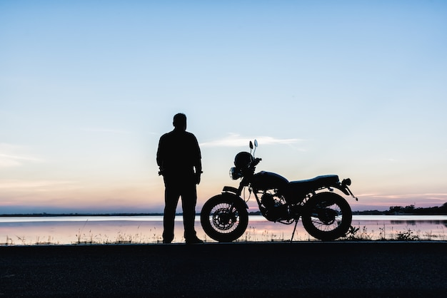 The silhouette of a biker standing leisure travelers and  motorcycle on the road Premium Photo