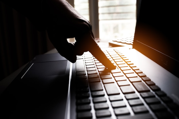 Silhouette black and white hands of anonymous hackers typing