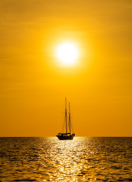 Silhouette boat in sea and ocean with beautiful sunset sky Premium Photo