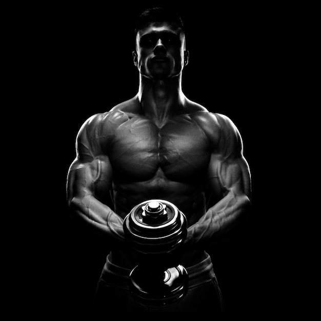 Silhouette of a bodybuilder pumping up muscles with dumbbell Premium Photo