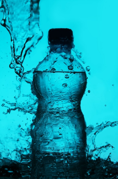Silhouette of bottle with water splashes Free Photo