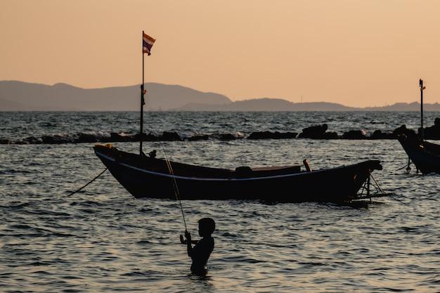 Silhouette of boy fishing in the sea Premium Photo