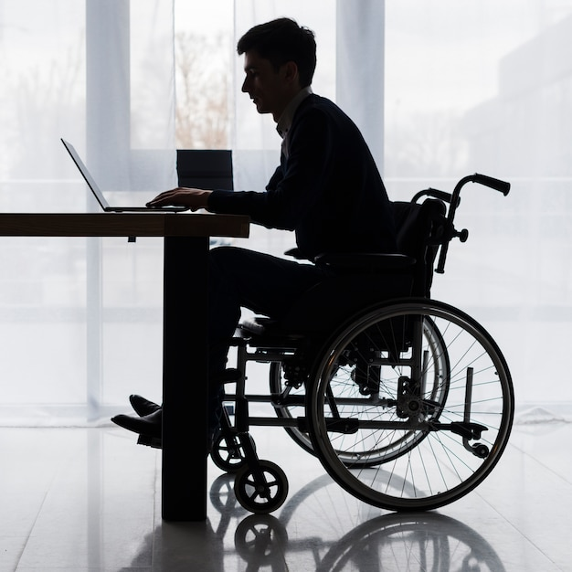 Silhouette of a businessman sitting on wheelchair using laptop on table Free Photo