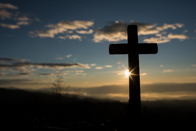 Silhouette of catholic cross and sunrise Free Photo