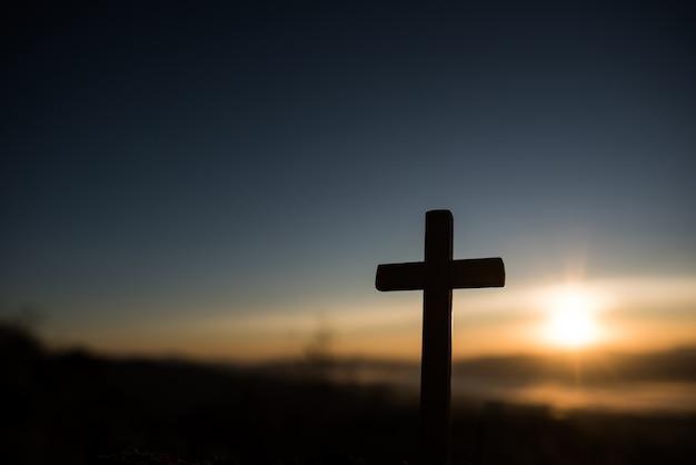 Silhouette of catholic cross and sunrise Free Photo