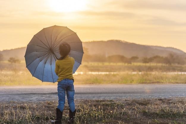 Silhouette children with umbrella at sunset Premium Photo
