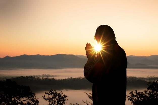 Silhouette of christian man hand praying, spirituality and religion, man praying to god. Free Photo