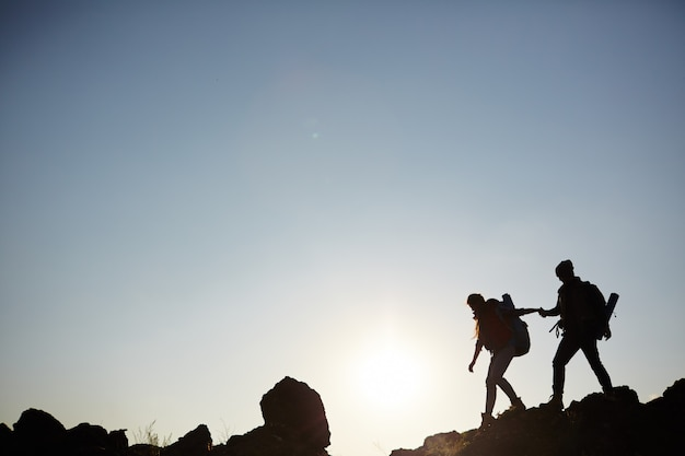 Silhouette of couple climbing mountains Free Photo
