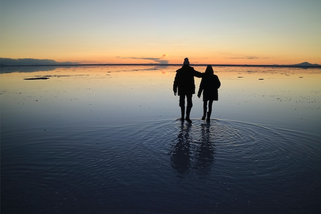 Silhouette of a couple exploring the incredible mirror effect of uyuni salt flats, bolivia Premium Photo