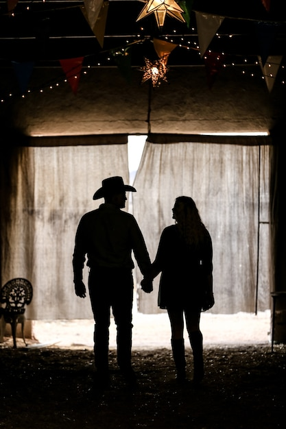 Silhouette of a couple holding hands in a tent under the lights Free Photo