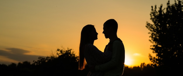 Silhouette couple kissing over sunset, profiles of romantic couple looking at each othe Premium Photo