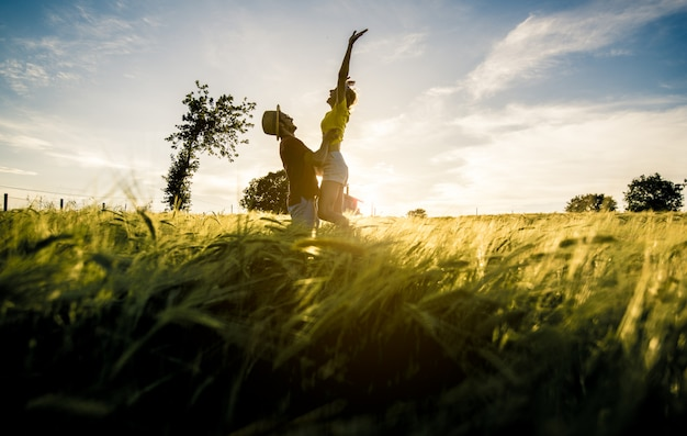Silhouette of a couple in love jumping with raised arms on a wheat field at sunset. Premium Photo
