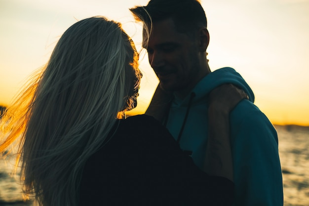 Silhouette of couple in love on the pier, sunset time Premium Photo