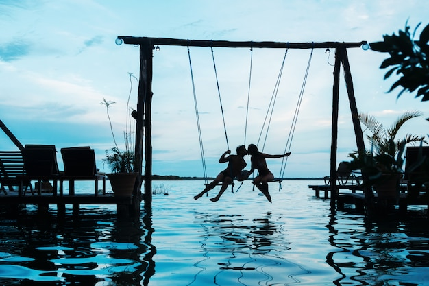 Silhouette of couple on the swings Premium Photo