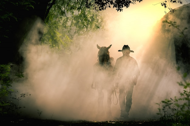 The silhouette of the cowboy and the horse in the morning sunrise Premium Photo