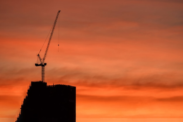 Silhouette crane and building construction at dusk Premium Photo
