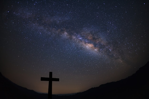 Silhouette of cross over milky way background Premium Photo